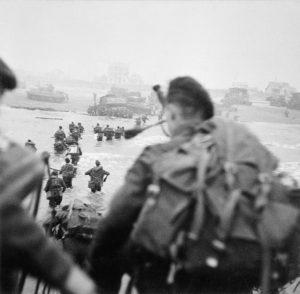 Piper Bill Millin est au premier plan, Lord Lovat, sur la droite dans la colonne, marchant dans l'eau.